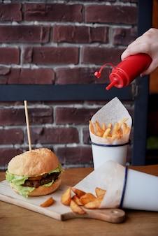 Pommes frites, schweinekotelett-hamburger und sauce auf einem schneidebrett