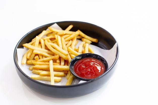 Pommes-frites und ketschup in einem schwarzen teller oben gedient auf einem tabellenabschluß.