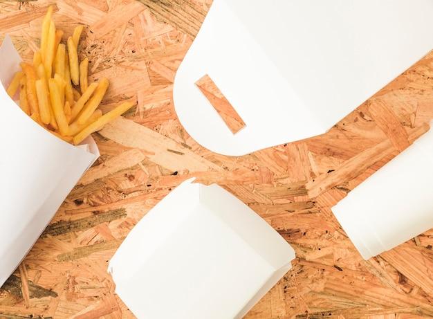 Pommes-frites und weißes paketmodell auf hölzernem hintergrund