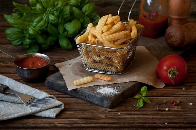 Pommes-friteskartoffeln, tomatenketschup und senf auf rustikalem hölzernem hintergrund.