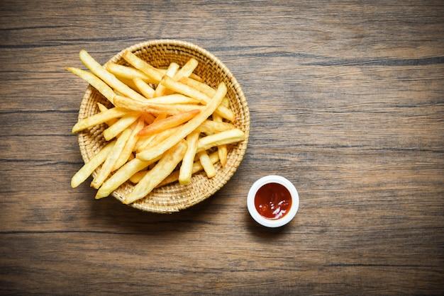 Pommes-friteskorb und -ketschup auf hölzernem speisetischhintergrund