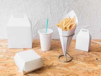 Pommes frittes; Wegwerfschale und Lebensmittelpaketspott oben auf hölzernem Beschaffenheitshintergrund