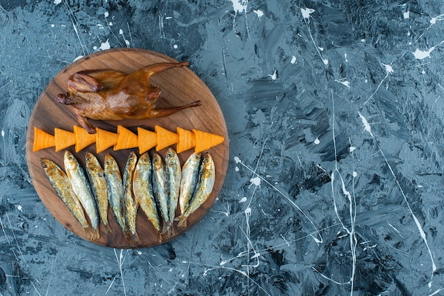 Pommes, grill huhn und fisch auf einem brett, auf dem marmorhintergrund.