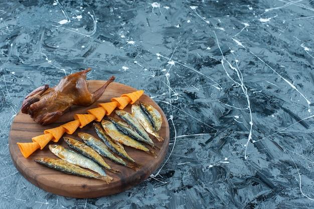 Pommes, grillhähnchen und fisch auf einem brett, auf dem marmortisch.