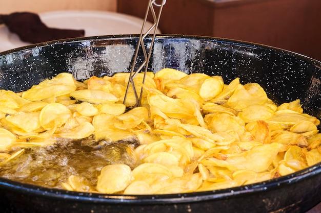 Pommes in einer schwarzen pfanne mit viel kochendem öl braten