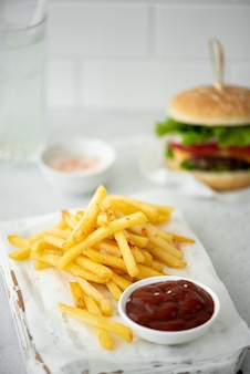 Pommes mit tomatenketchup und hamburger auf weißem tisch