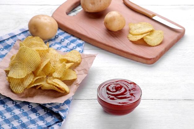 Pommes, snacks und rote sauce auf einem weißen holztisch