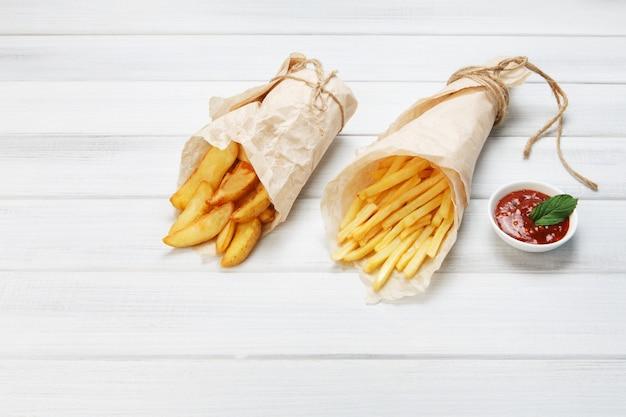 Pommes und keile kartoffeln auf einem holztisch