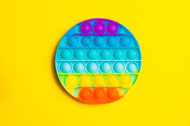 Pop it anti-stress auf eine gelbe oberfläche. modernes spielzeug. spielzeug für kinder. silikon spiel. autismus.