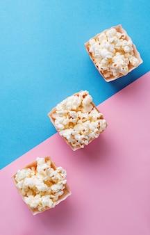 Popcorn auf blauem und rosafarbenem hintergrund