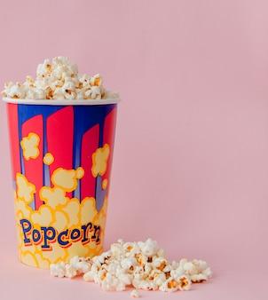Popcorn auf einem pastellrosa hintergrund und einem platz für text. flach liegen. copyspace. kinokonzept. hintergrund