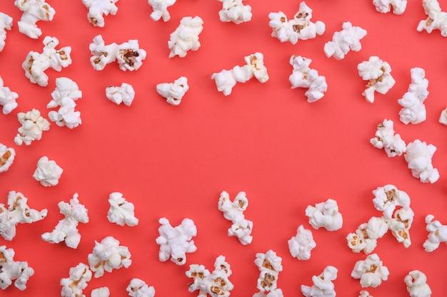 Popcorn auf rotem hintergrund draufsicht nahaufnahme