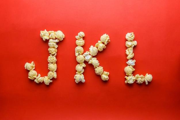 Popcorn bilden buchstaben j, k, l auf rotem grund