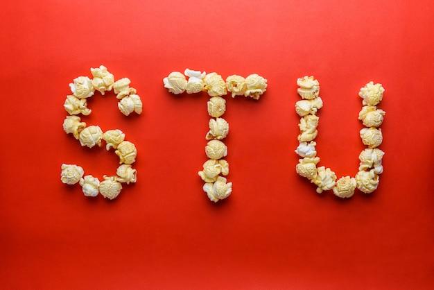 Popcorn bilden buchstaben s, t, u auf rotem grund