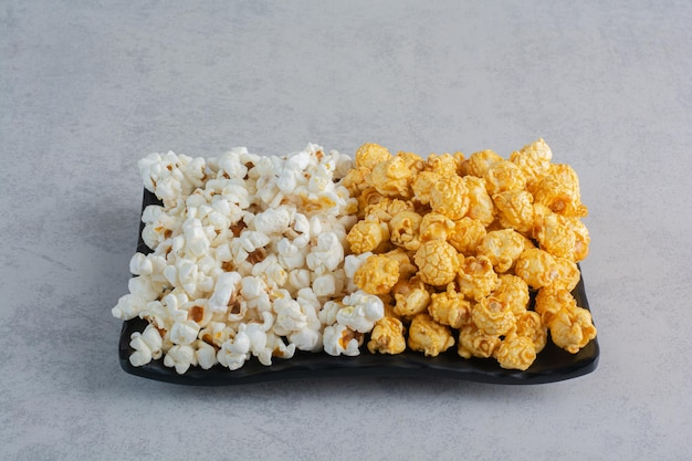 Popcorn-bonbons und einfaches popcorn auf einer platte auf marmoroberfläche
