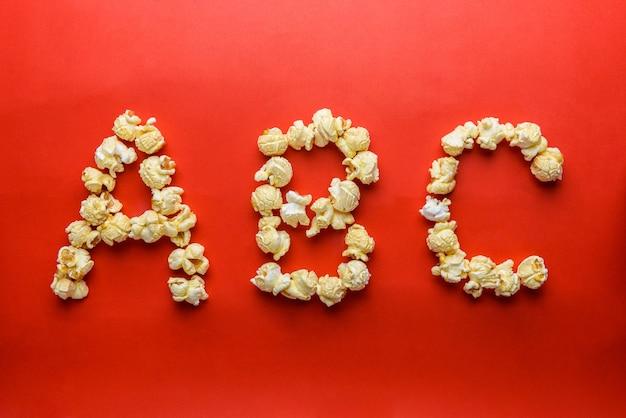 Popcorn, das buchstaben a, b, c auf rotem hintergrund bildet