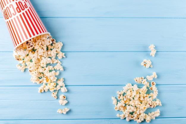 Popcorn horizontale banner. rot entfernte papierschale und kerne, die auf blauem hölzernem hintergrund liegen.