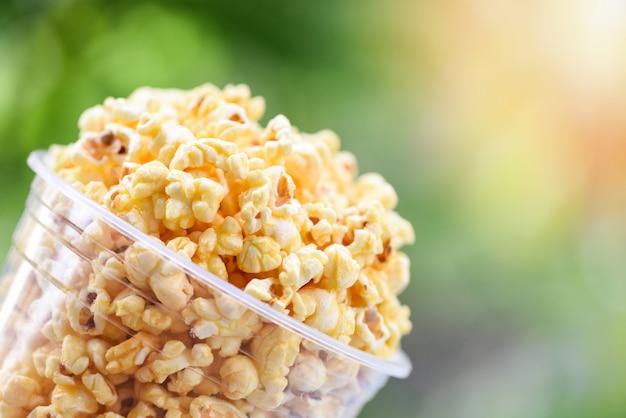 Popcorn im cup und naturgrün und sonnenlicht backgroubd / süßes butterpopcornsalz