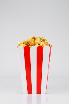 Popcorn im karamellsirup im papierkasten auf dem tisch