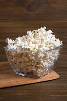 Popcorn in der glasschüssel auf hölzernem