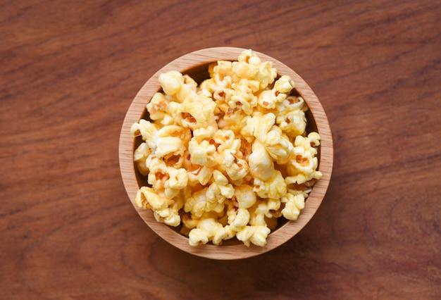 Popcorn in der hölzernen schalenschüssel und in der draufsicht des hölzernen backgroubd / süßes butterpopcornsalz