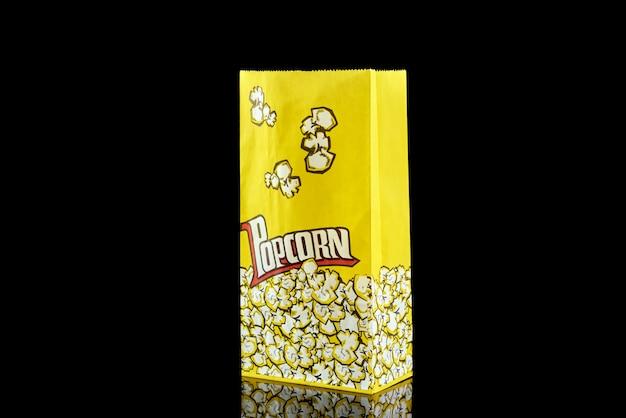 Popcorn in der papiertüte auf schwarzem hintergrund