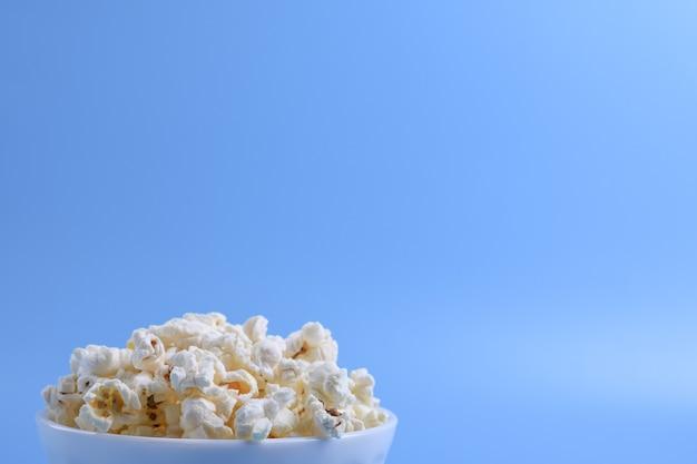Popcorn in der schüssel auf einem blauen hintergrund. nahansicht. draufsicht.