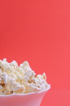 Popcorn in der schüssel auf einem roten hintergrund. nahansicht. vorderansicht