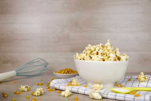 Popcorn in der weißen schüssel mit pastelllöffel-, salz-, handmischer- und maissamen auf hölzernem hintergrund