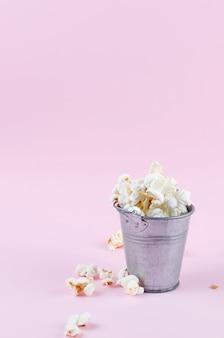 Popcorn in einem eimer auf rosa