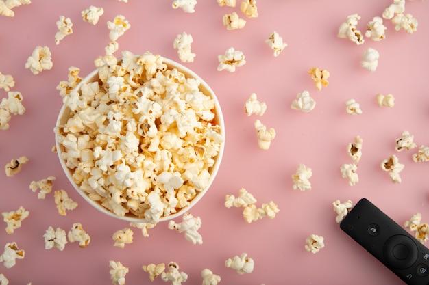 Popcorn in einem papierkasten oder in einer gestreiften papierschale angesehen von oben lokalisiert auf rosa