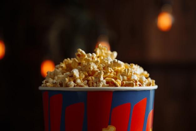 Popcorn in einer hellen box auf hölzernem hintergrund. nahaufnahme.