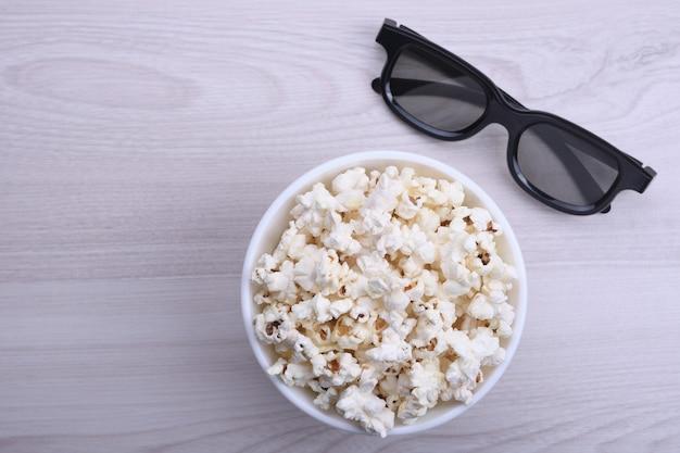 Popcorn in einer schüssel und 3d-gläser auf einem hellen hölzernen hintergrund. sicht von oben. freier platz für text.