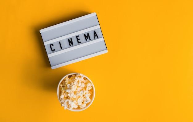 Popcorn in einer vase mit text cinema auf weißem leuchtkasten isoliert auf gelb. flaches banner, draufsicht. ins kino gehen.