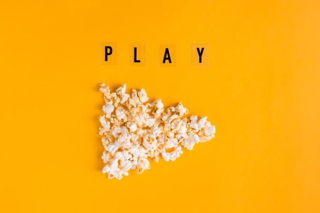 Popcorn in form von play-button und text play auf gelbem hintergrund. flaches lay-banner, ansicht von oben. um zum kinokonzept zu gehen. ich schaue gerne filme.