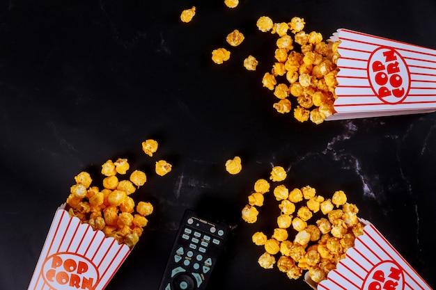 Popcorn in gestreiften kisten auf schwarzer oberfläche mit fernbedienung verschüttet