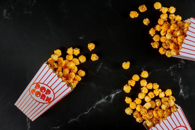 Popcorn in gestreiften kisten auf schwarzer oberfläche verschüttet