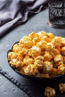 Popcorn in karamellglasur in einem teller auf einem dunklen betontisch.