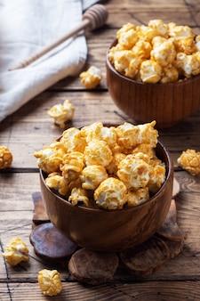 Popcorn in karamellglasur in holztellern auf einem rustikalen tisch.