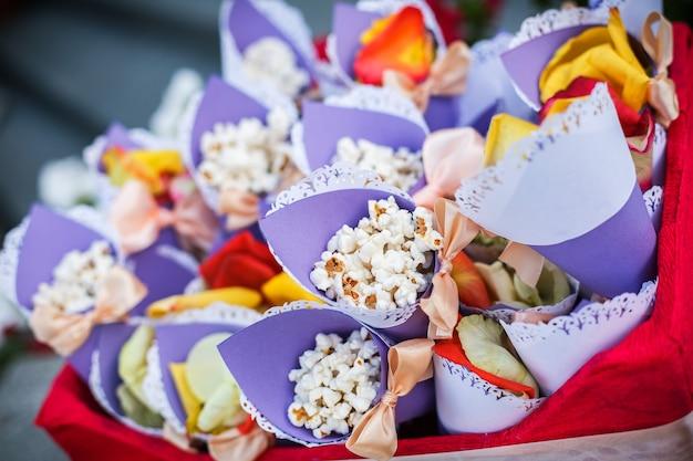 Popcorn in schönen papierrollen mit schleifen als geschenk an gäste bei der hochzeit