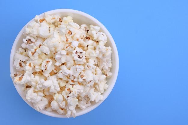 Popcorn in schüssel auf blauem grund. nahaufnahme. ansicht von oben