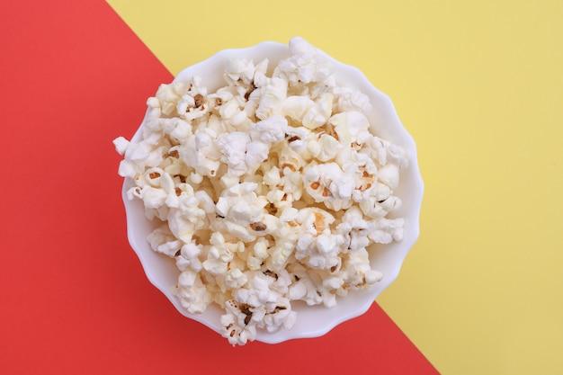 Popcorn in schüssel auf rotem grund. nahaufnahme. ansicht von oben.