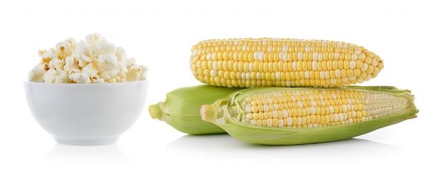 Popcorn in schüssel und mais lokalisiert auf weißem hintergrund