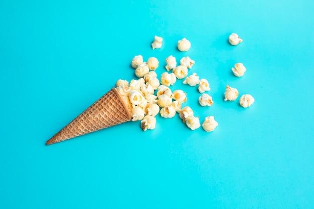 Popcorn mit eistüte auf pastellfarbenem hintergrund