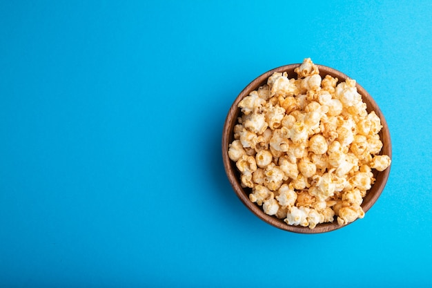 Popcorn mit karamell in der holzschale auf einem pastellblauen hintergrund. draufsicht, flache lage, kopierraum.