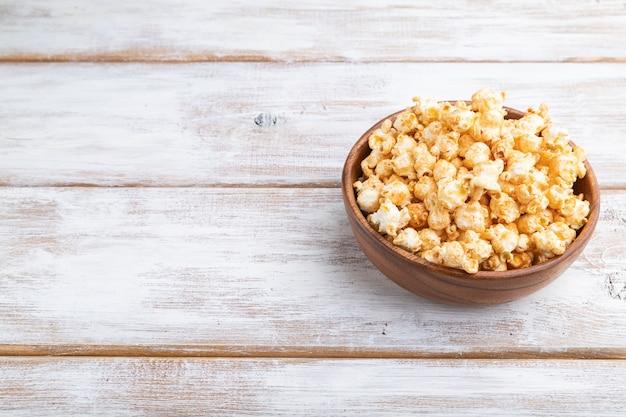 Popcorn mit karamell in der holzschale auf einem weißen hölzernen hintergrund. seitenansicht, kopierraum.
