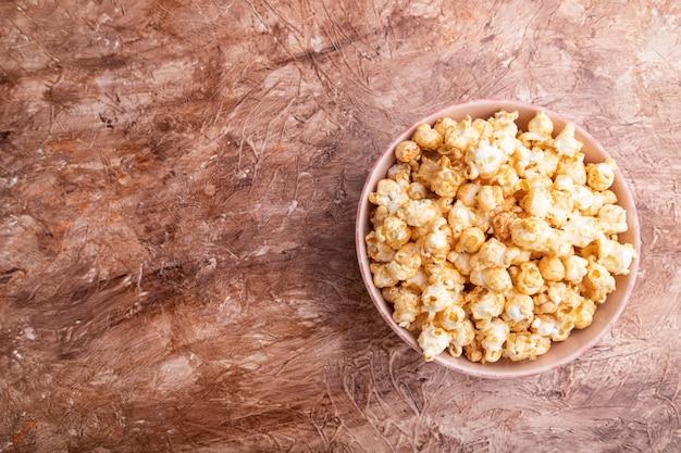 Popcorn mit karamell in der keramikschale auf braunem betonhintergrund. draufsicht, flache lage, kopierraum.