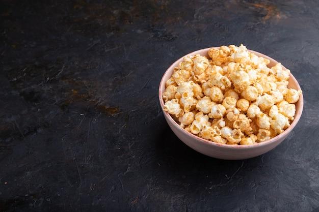 Popcorn mit karamell in der keramikschale auf einem schwarzen betonhintergrund. seitenansicht, kopierraum.
