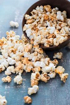 Popcorn mit karamellgeschmack wird aus der schüssel gestreut
