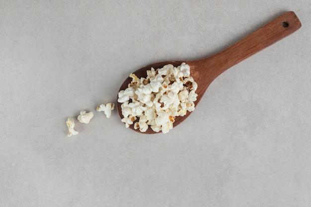 Popcorn mit klassischem geschmack auf einem holzlöffel auf marmor.